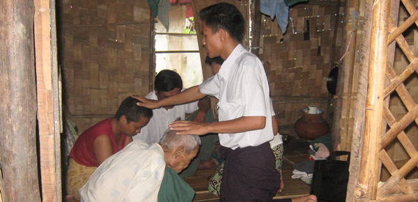 Native missionary lays hands on a sick buddhist as prayers are offerd to God for healing